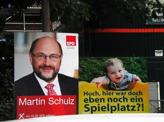 Nebeneinander zweier plakate im sommer des jahres 2017. Zur linken das personenwahlkampfplakat Martin Schulz der SPD, das überall wie spämm plakatiert wurde, zur rechten ein plakat mit dem text: 'huch, hier war doch eben noch ein spielplatz?!'.