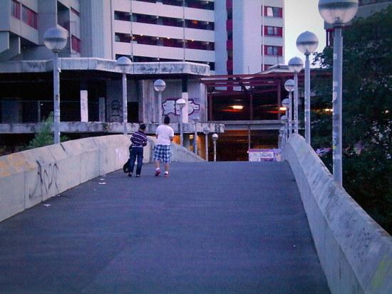 Zwei kinder gehen über eine brücke in die zerfallende brutalistische betonburg des ihmezentrums -- ein bild wie aus einem deprimierenden dystopischen film