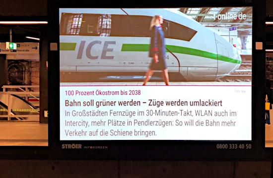 Foto eines ströer-werbebildschirms in einer u-bahn-stazjon: 100 Prozent Ökostrom bis 2038 -- Bahn soll grüner werden, Züge werden umlackiert -- In Großstädten Züge im 30-Minuten-Takt, WLAN auch im Intercity, mehr Plätze in Pendlerzügen: So will die Bahn mehr Verkehr auf die Schiene bringen