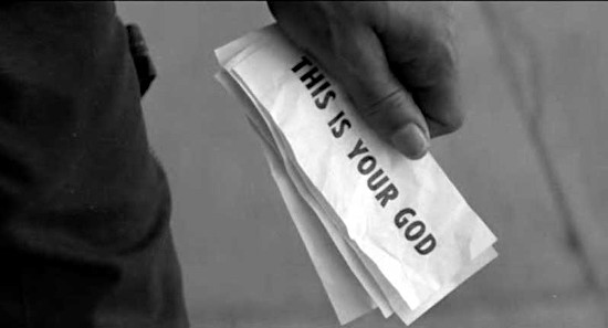 Standbild aus dem film 'they live'. Zu sehen ist eine hand, die banknoten hält. Auf den banknoten ist die unterschwellige botschaft 'THIS IS YOUR GOD' sichtbar.
