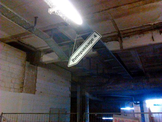 Foto aus dem sockelgeschoss. Ein hinter einem bauzaun relativ neu, aber provisorisch aufgehängtes wegweiserschild zur ihmepassage 4 hängt schief an der decke. Drumherum nur dreck und zerfall.