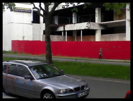Stark mit Gimp nachbearbeitetes (älteres) Foto des Ihmezentrums, von der Blumenauer Straße aus gesehen. An der Fassade der Ruine hängt noch die alte Reklame einer Spielhalle mit dem Text 'Spielparadies'.