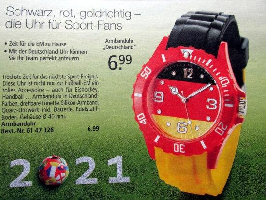 Werbung für ein grottenhässliches tinnef-produkt zur kommenden UEFA-europameisterschaft -- »Schwarz, rot, goldrichtig -- die Uhr für Sportfans -- Armbanduhr Deutschland, 6,99 € -- Zeit für die EM zu Hause -- Mit der Deutschland-Uhr können Sie Ihr Team perfekt anfeuern -- Höchste Zeit für das nächste Sport-Ereignis. Diese Uhr ist nicht zur Fußball-EM ein tolles Accessoire, auch für Eishockey, Handball... Armbanduhr in Deutschland-Farben, drehbare Lünette, Silikon-Armband, Quarz-Uhrwerk inkl. Batterie, Edelstahl-Boden, Gehäusedurchmesser 40 mm. -- Armbanduhr Best.-Nr. 61 47 326, 6,99 €«