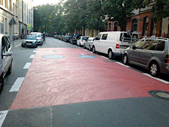 Rot eingefärbter bereich auf der fahrbahn der noltestraße in hannover-linden, mit aufgebrachten fahrradpiktogrammen in form des verkehrszeichens radweg